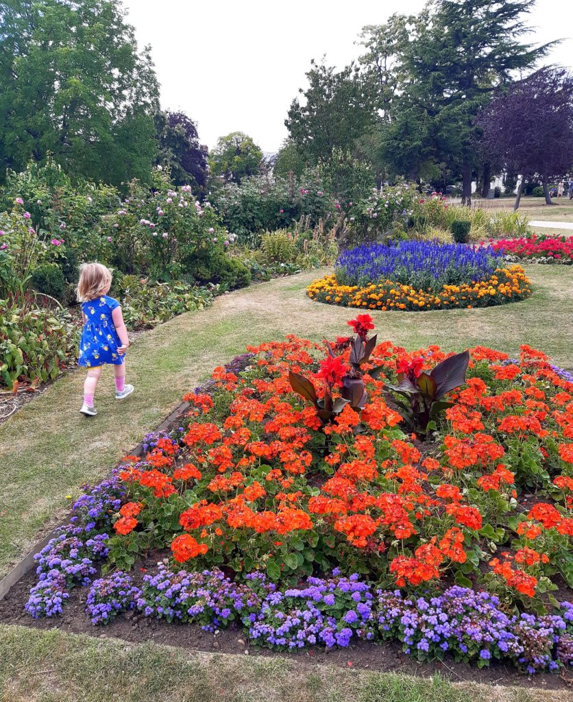 A park filled with bright flowers, and a little girl walking through it.